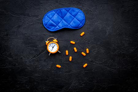 Medicine helps get asleep. Good sleep. Sleeping pills near sleeping mask and alarm clock on black background top view. Reklamní fotografie