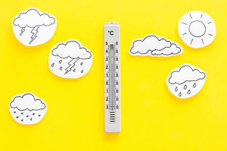 Weather forecast concept. Air temperature. Thermometer among cloud and lightening, sun, rainy clouds on yellow background top view. Stockfoto