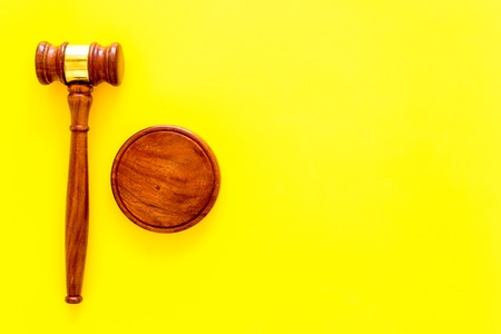 Lawyer or attorney concept. Judge gavel on yellow background top view. Фото со стока
