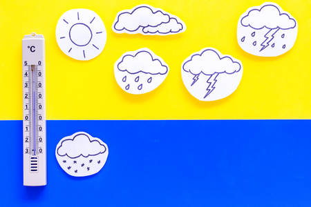 Weather forecast concept. Air temperature. Thermometer among cloud and lightening, sun, rainy clouds on yellow and blue background top view.