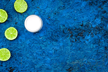 Organic citrus cosmetics for skin care. Lemon or lime moisturizing cream on blue background top view copy space Stock Photo