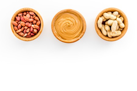 Peanut paste concept. Bowls with butter, nuts in shell, peeled nuts on white background top view.