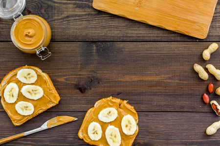 Sandwich with nut butter and banana for breakfast. Toast, knife and glass jar with nut paste, nuts on dark wooden background. Stock Photo