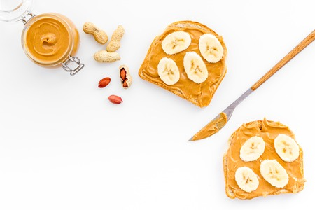 Sandwich with nut butter and banana for breakfast on white background top view.