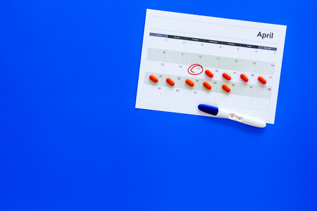 Planning pregnancy. Positive pregnancy test near calendar page and pills on blue background top view.