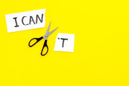 I can concept. Encourage yourself. Scissors cut off the letter t of written word I cant. Yellow background top view.