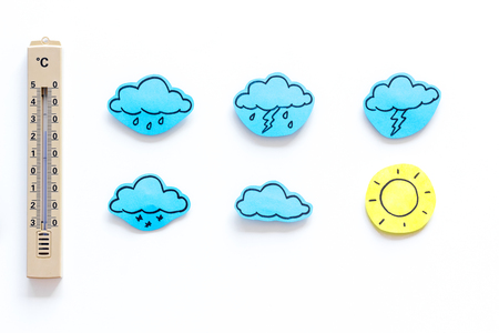 Weather forecast concept. Air temperature. Thermometer among cloud and lightening, sun, rainy clouds on white background top view. Stock Photo