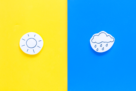 Good and bad weather concept. Template for forecast. Sun vs rainy cloud on yellow and blue background top view.