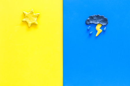 Good and bad weather concept. Template for forecast. Sun vs cloud and lightening with rain on yellow and blue background top view copy space Stockfoto