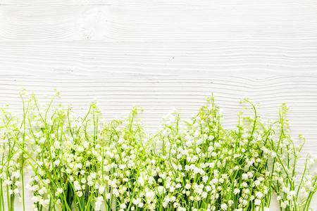 Lily of the valley Bloemenlijst. Lente achtergrond op witte bureau bovenaanzicht kopie ruimte Stockfoto