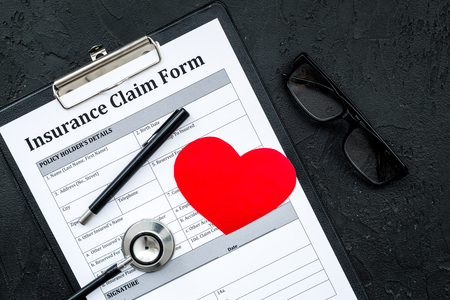 Health insurance claim form for fill out. Empty form near heart sign and stethoscope on black background.