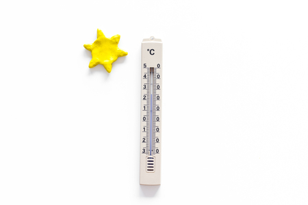 Clear weather concept. Air temperature. Thermometer near sun on white background top view copy space