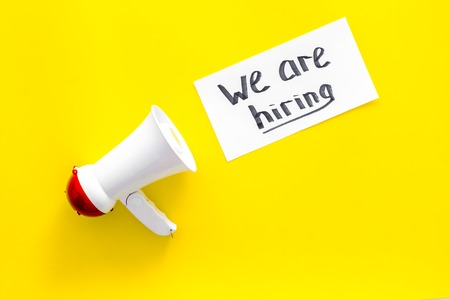 Job recruiting advertisement. We are hiring lettering near megaphone on yellow background top view copy space Stock Photo