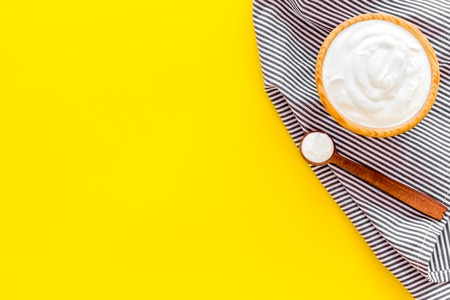 Food helps digestion. Greek yogurt in brown bowl near spoon on blue tablecloth, yellow background top view copy space