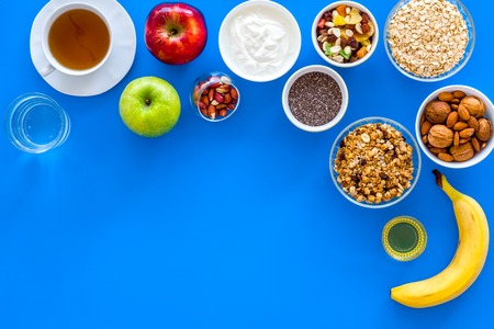 Make a menu for wholesome breakfast. Fruits, oatmeal, yogurt, nuts, crispbreads, chia on blue background top view copy space