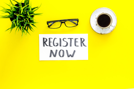 Membership concept. Template for registration. Register now hand lettering icon on word desk with glasses, coffee, plant on yellow background top view space for text