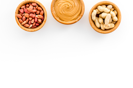Peanut paste concept. Bowls with butter, nuts in shell, peeled nuts on white background top view copy space Stock Photo
