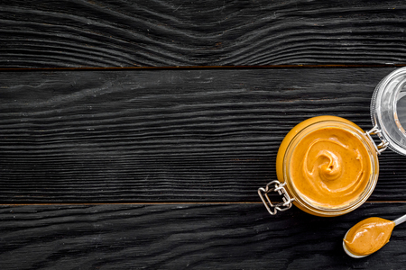 Nut butter in glass jar and spoon with butter on black woodenbackground top view copy space Stock fotó