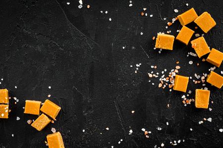 Trendy dessert. Salted caramel. Caramel cubes sprinkled by salt crystals on black background top view.
