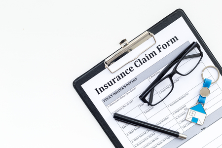 Real estate insurance. Insurance claim form near house keychain on white background top view copy space