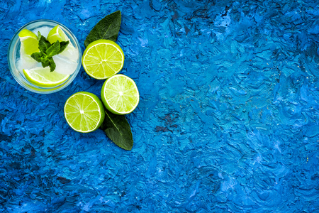 Tropical cocktail. Beverage which women likes. Glass of mojito with slices of lime, mint, ice cubes on blue background top view copy space