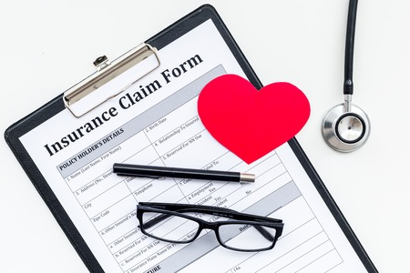 Health insurance claim form for fill out. Empty form near heart sign and stethoscope on white background top view