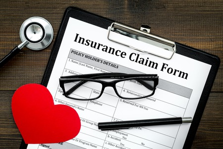 Health insurance claim form for fill out. Empty form near heart sign and stethoscope on dark wooden background top view
