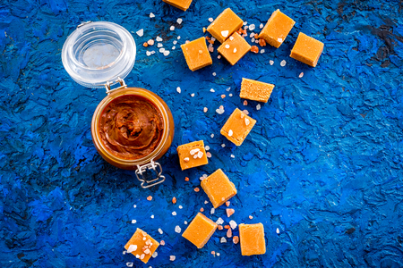 Contrast of flavors. The combination of salty and sweet. Caramel sauce in glass jar near caramel cubes on blue background top view copy space