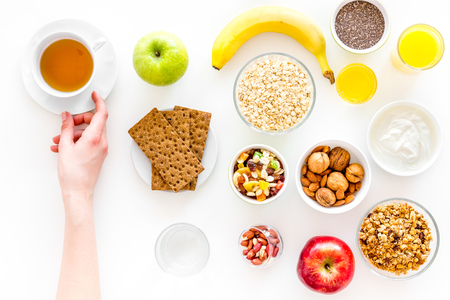 Ingredients for healthy breakfast. Fruits, oatmeal, yogurt, nuts, crispbreads, chia on white background top view