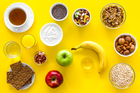 Layout of products for healthy and hearty breakfast. Fruits, oatmeal, yogurt, nuts, crispbreads, chia on yellow background top view copy space