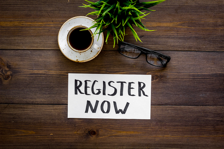 Membership concept. Template for registration. Register now hand lettering icon on word desk with glasses, coffee, plant on dark wooden background top view space for text
