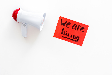 Job recruiting advertisement. We are hiring lettering near megaphone on white background top view copy space Stock Photo