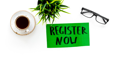 Membership concept. Template for registration. Register now hand lettering icon on word desk with glasses, coffee, plant on white background top view space for text