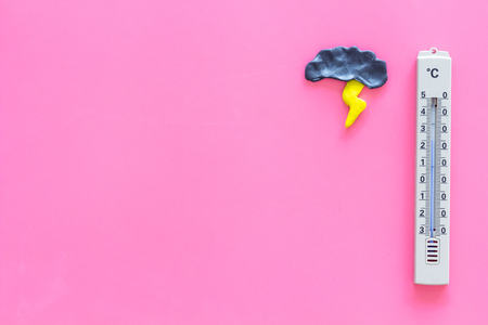 Storm weather concept. Air temperature. Cloud and lightening near thermometer on pink background top view copy space