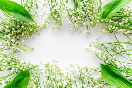Lily of the valley flowers frame. Spring background on white desk top view.