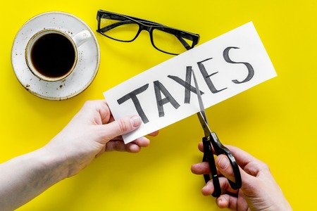 Tax reduce concept. Hands with scissors cut paper with word Taxes on yellow background with coffee and glasses top view