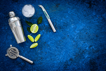 Process of making mojito concept. Ingredients and crockery. Slices of lime, mint, glass with ice cubes, shaker, strainer on blue background top view copy space