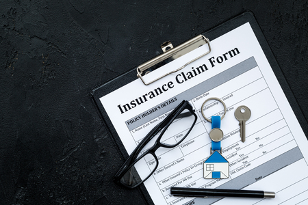 Real estate insurance. Insurance claim form near house keychain on black background top view copy space