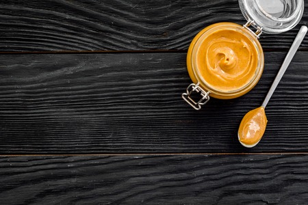 Nut butter in glass jar and spoon with butter on black wooden background top view copy space