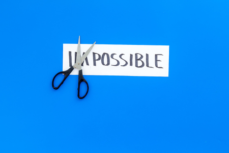 Belief in yourself concept. Cutting the part im of written word impossible by scissors. Blue background top view copy space Stock Photo