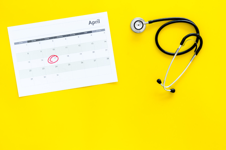 Planning medical examination concept. Regular medical examinations. Calendar with date circled and stethoscope on yellow background top view copy space Stock Photo