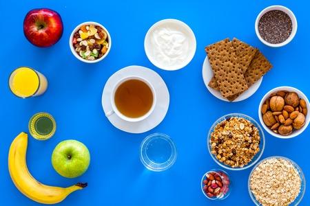 Make a menu for wholesome breakfast. Fruits, oatmeal, yogurt, nuts, crispbreads, chia on blue background top view