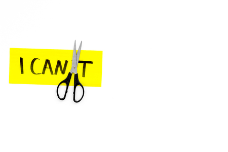 I can concept. Motivate yourself, believe in yourself. Scissors cut the letter t of written word I cant. White background top view copy space Banco de Imagens