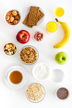 Ingredients for healthy breakfast. Fruits, oatmeal, yogurt, nuts, crispbreads, chia on white background top view