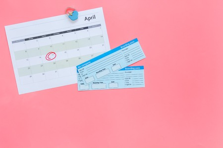 Plan a trip. Buy airplane tickets. Tickets near calendar with date circled on pink background top view copy space
