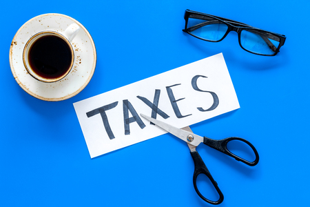 Tax reduce concept. Scissors and paper with word Taxes on blue background with coffee and glasses top view