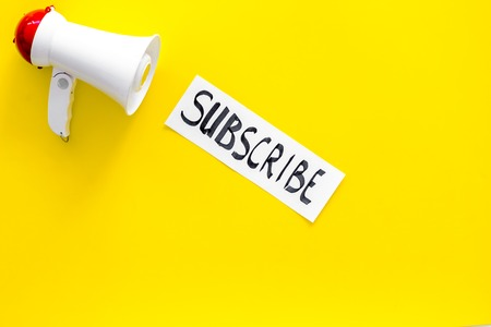 Subscribe template or mockup. Hand lettering subscribe near megaphone on yellow background top view space for text Imagens