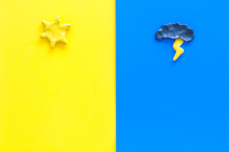Good and bad weather concept. Template for forecast. Sun vs cloud and lightening on yellow and blue background top view copy space