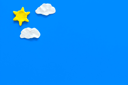 Clear and cloudy weather icons on blue background top view copy space Reklamní fotografie