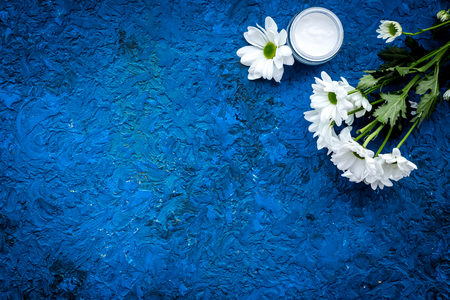 Hypoallergenic baby cream. Chamomile cream in small jar near chamomile flowers on blue background top view copy space Stock Photo